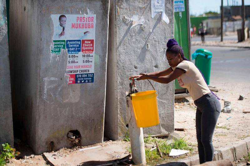 A woman fills a bucket from a communal tap in front of a line of communal toilets in Khayelitsha, near Cape Town, on March 31, 2020. - Local government administrators in Cape Town said on March 29, 2020, a COVID-19 coronavirus case had been detected in Khayelitsha, the city's largest township, where hundreds of thousands live in shacks.  An outbreak in the crowded townships where water and sanitation are problematic, could prove difficult to contain in the country which already has the highest number of infections in Africa. (Photo by RODGER BOSCH / AFP)
