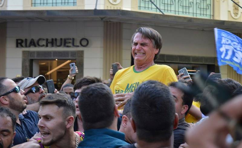 In this Sept. 6, 2018 photo, presidential candidate Jair Bolsonaro grimaces right after being stabbed in the stomach during a campaign rally in Juiz de Fora, Brazil. Bolsonaro, a leading presidential candidate in Brazil, was stabbed during the campaign event, though officials and his son said the injury is not life-threatening. (AP Photo/Raysa Leite)