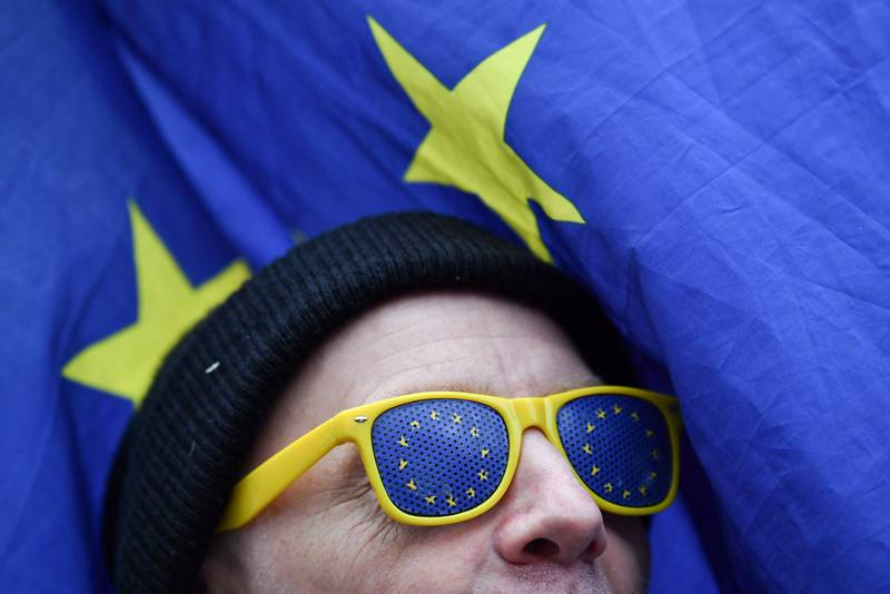 """TOPSHOT - An anti-Brexit protester is seen wearing glasses with EU flag motifs with an EU flag in the background outside the Houses of Parliament in London on January 10, 2019. - Britain's business minister on Thursday warned that the prospect of crashing out of the European Union without an agreement would be """"disastrous"""" for the country, as fractious MPs prepare to vote on a contentious Brexit deal. (Photo by Ben STANSALL / AFP)"""