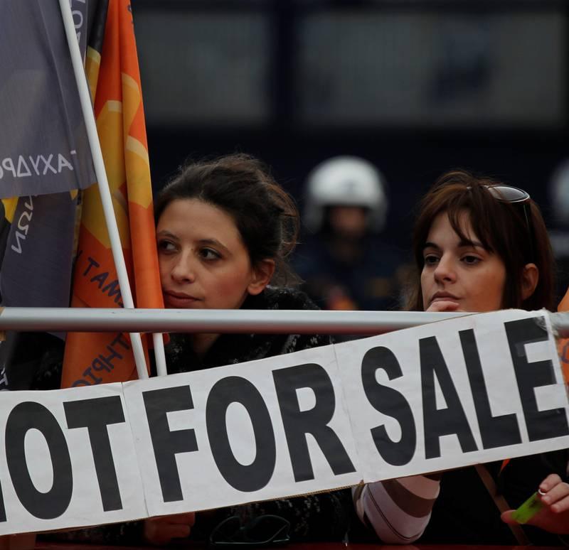 Greske arbeidere protesterer utenfor den statlige banken Hellenik PostBank under sommerens gjeldskrise. FOTO: NTB SCANPIX