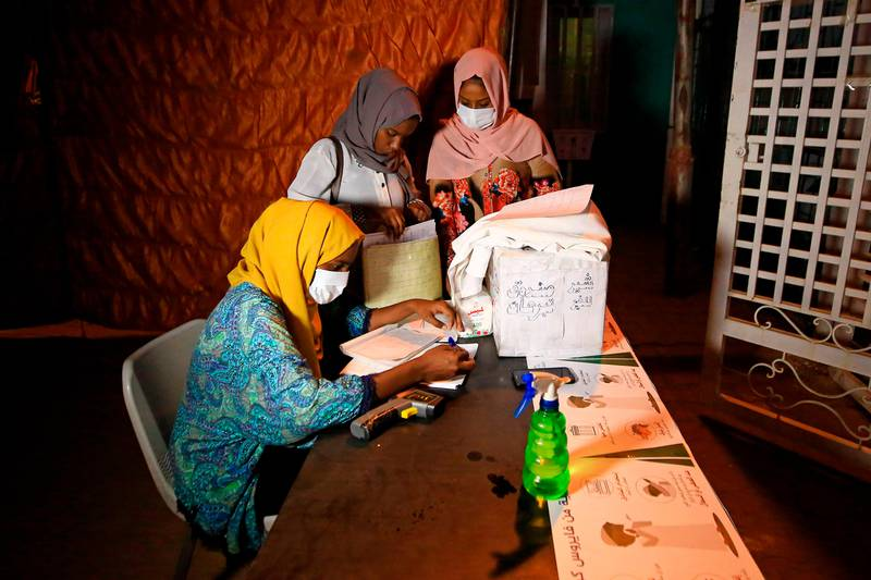 Volunteer pharmacists, wearing protective masks, work at a small treatment centre set up by locals in the Shambat district of northern Khartoum on June 18, 2020, amid acute shortage of medicine as Sudan fights to control the spread of COVID-19 coronavirus. - As it battles mounting coronavirus cases, Sudan is grappling with acute scarcity of essential medications amid growing economic woes largely blamed on policies of ousted president Omar al-Bashir. Health care providers have recently reported pervasive shortages of basic medications in pharmacies and hospitals. And patients, suffering from critical diseases, say they struggle to find desperately-needed drugs. (Photo by ASHRAF SHAZLY / AFP)
