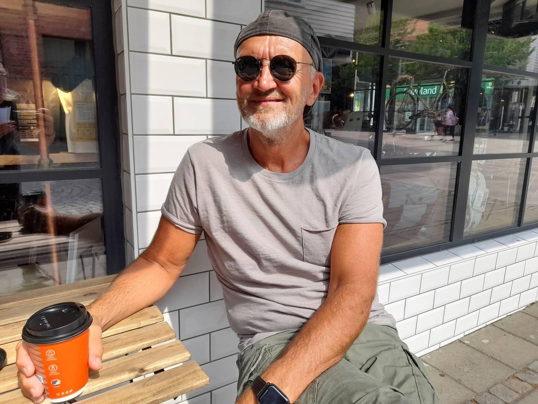 Solbrun mann med bakovervendt caps og mørke solbriller sitter utenfor Choco Loco