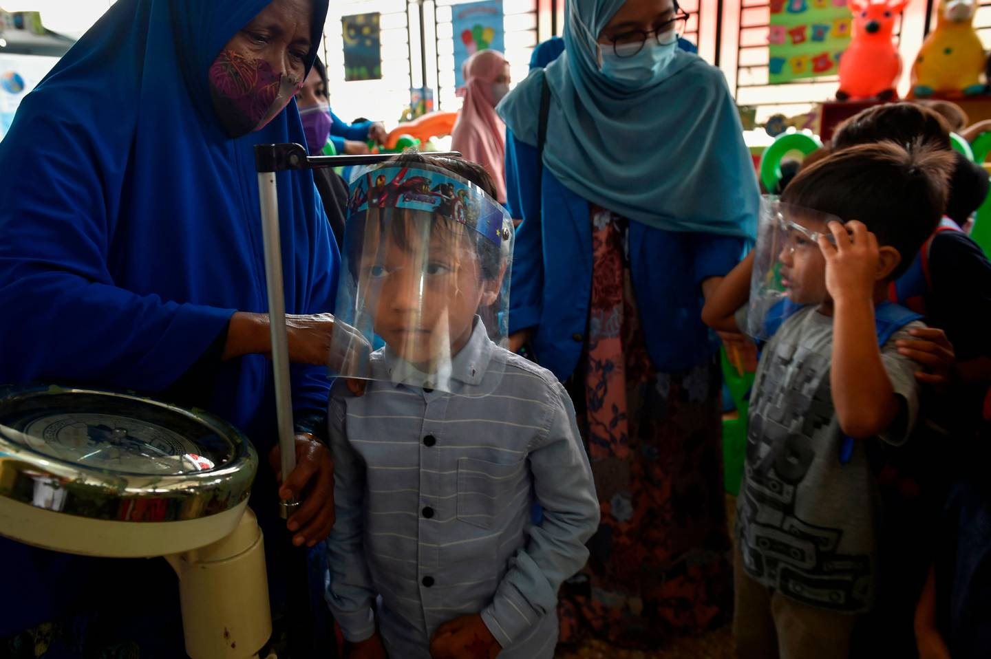 A child's measurements are taken before receiving the measles and polio vaccines at a service post in Banda Aceh on November 4, 2020. (Photo by CHAIDEER MAHYUDDIN / AFP)