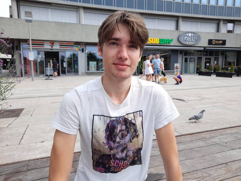 En ung mann i hvit t-skjorte på benk på Stortorvet, Fredrikstad