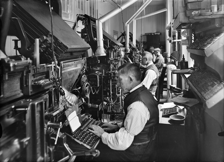 Settemaskiner ble utvikla allerede på 1820-tallet, men kom for alvor i bruk med Linotype-maskina fra 1886. Da fikk typografene mindre befatning med blystøv og farge, og kunne dermed ha hvite skjorter som arbeidsantrekk – «hvitsnipparbeidere». Foto fra Emil Moestue trykkeri i Norbygata 12 i 1938.