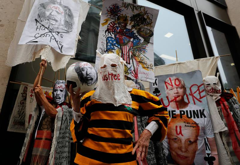 British Fashion designer Vivienne Westwood, center, with her head covered, poses for photos during a protest to support Julian Assange outside the Central Criminal Court Old Bailey in London, Monday, Sept. 7, 2020. Lawyers for WikiLeaks founder Julian Assange and the U.S. government were squaring off in a London court on Monday at a high-stakes extradition case delayed by the coronavirus pandemic. American prosecutors have indicted the 49-year-old Australian on 18 espionage and computer misuse charges over Wikileaks' publication of secret U.S. military documents a decade ago. The charges carry a maximum sentence of 175 years in prison. (AP Photo/Frank Augstein)