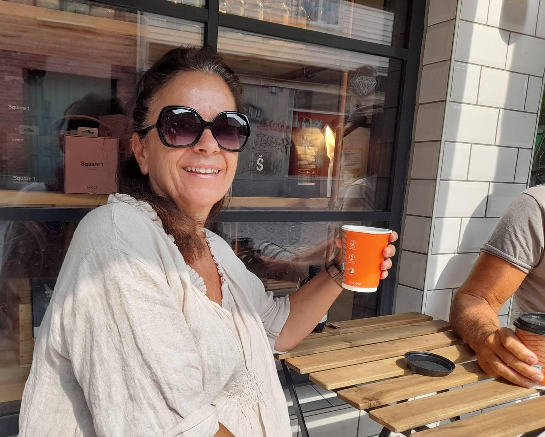 Kvinne med solbriller, holder en kaffekopp og smiler, utenfor Choco Loco