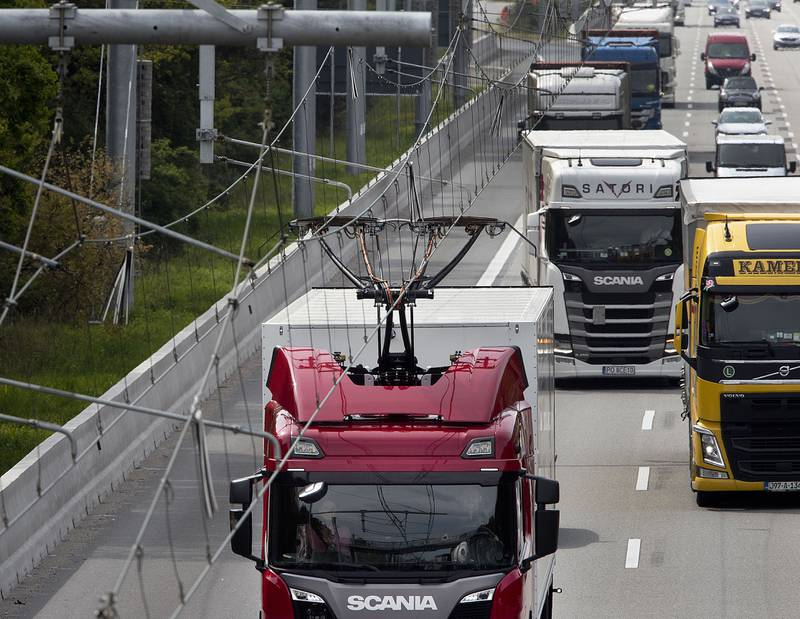 A hybrid truck that is equipped with a pantograph picks up power from power lines that are installed on a 5 km long highway section near Frankfurt, Germany, Tuesday, May 7, 2019. Germany's first so called electric highway was officially opened on Tuesday. So far only five trucking companies take part in the project. (AP Photo/Michael Probst)