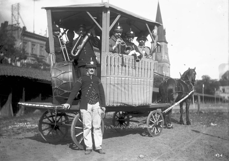 Musikanter på Barnehjelpsdagen 8. juni 1908 på Kontraskjæret med Johanneskirken i bakgrunnen. Her startet opptøyene denne dagen.