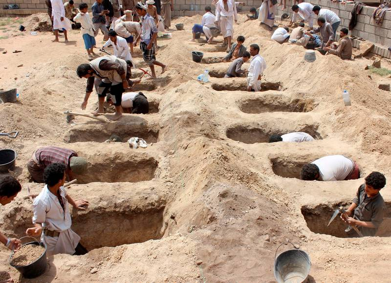 """(FILES) In this file photo taken on August 10, 2018 Yemenis dig graves for children, who where killed when their bus was hit during a Saudi-led coalition air strike, that targeted the Dahyan market the previous day in the Huthi rebels' stronghold province of Saada. - UN launches new talks on September 3, 2018, in Geneva to end the """"dirty war"""" in Yemen, a forgotten conflict causing the worst humanitarian crisis in the world. But an agreement seems far away such the animosity between belligerents is huge. (Photo by - / AFP)"""