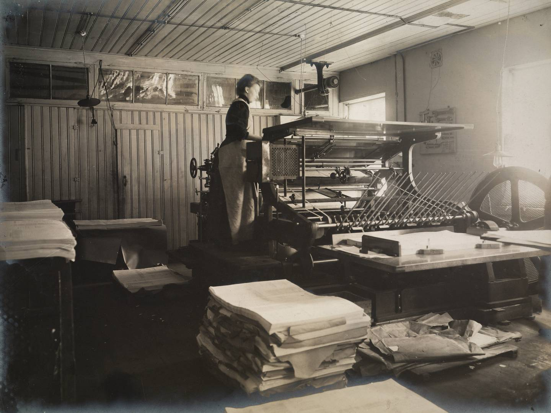 Påleggerskenes jobb var å stå oppe på selve trykkmaskina og mate pressa med papir. Jobben innebar også håndtering av tunge papirbunker eller -ris (i forgrunnen). Her en påleggerske ved Steenske bogtrykkeri og forlag i Rådhusgata 30 i 1910.
