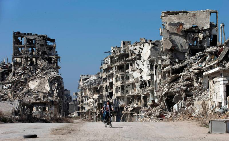 FILE - In this Feb. 26, 2016 file photo, a Syrian boy rides a bicycle through a devastated part of the old city of Homs, Syria. On Nov. 13, 1970, Hafez Assad a young career air force officer launched a bloodless coup. Fifty years later, Hafez Assad's family still rules Syria. The country is in ruins from a decade of civil war that killed around a half million people, displaced half the population and virtually wiped out the economy. But Hafez's son, Bashar Assad, has an unquestioned grip on what remains. (AP Photo/Hassan Ammar, File)