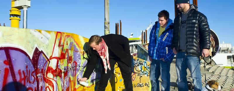 Eirik Faret Sakariassen (SV) sprayer rød spraymaling på den ene veggen i Geoparken. I teorien gjør han noe ulovlig, etter at kommunalstyret for miljø og utbygging vedtok nulltoleranse for tagging og fjerning av graffitiveggene i Geoparken tirsdag. Eldar Borge (SV) og graffitikunster Kim Stokke (til høyre) følger nøye med.