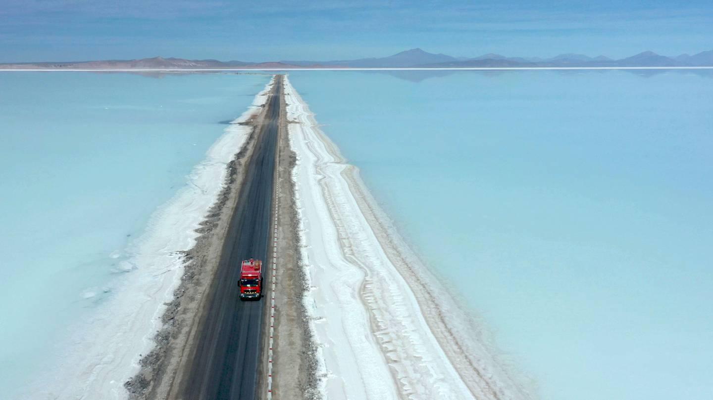 En lastebil kjører på en vei gjennom en slette med saltlake der litium utvinnes i Uyuni i Bolivia.