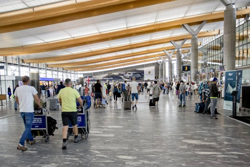 Bildet er av folk som går gjennom hallen på Oslo Lufthavn. De har bagasje på traller. Noen står ved skjermer for å sjekke inn og finne flytider. Foto: Hanna Johre / NTB