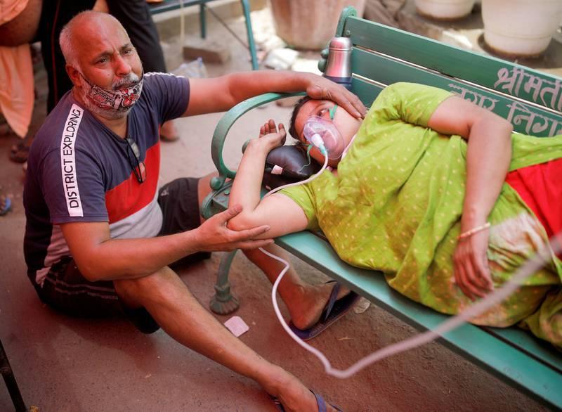 En mann sitter ved siden av kona, som har pusteproblemer og får oksygen utenfor et sikh-tempel i Ghaziabad, India.