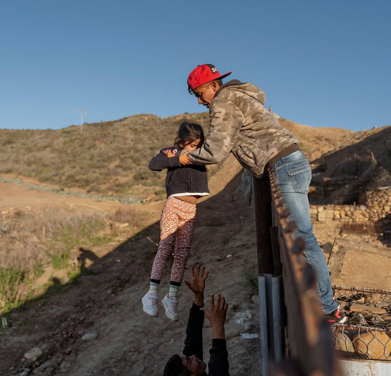GJERDE: En migrant fra Honduras løfter datteren sin over grensegjerdet ved San Diego. FOTO: DANIEL OCHOA DE OLZA/NTB SCANPIX