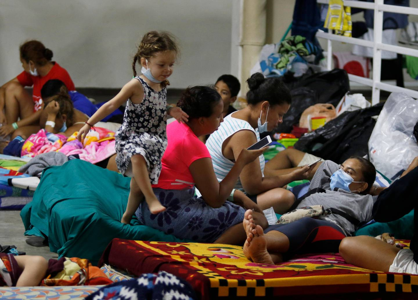 Hurricane victims take refuge in a shelter in San Pedro Sula, Honduras, Saturday, Nov. 21, 2020. Shelters for people whose homes were flooded or damaged by hurricanes Eta and Iota in Honduras are now so crowded that thousands of victims have taken refuge under highway overpasses or bridges. The Red Cross estimates that about 4.2 million people were affected by the back-to-back hurricanes in November in Honduras, Nicaragua and Guatemala. (AP Photo/Delmer Martinez)