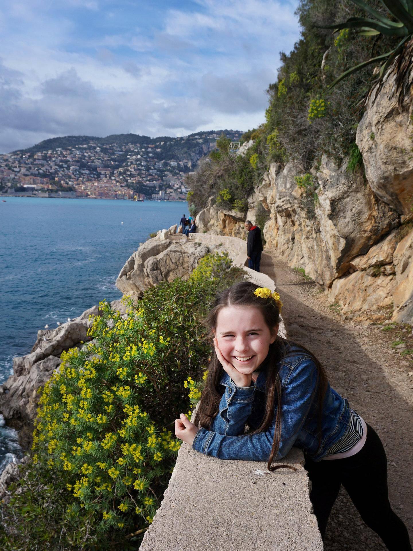 Kyststien klorer seg inn i de bratte klippeveggene. I bakgrunnen skimtes hyggelige Villefranche.