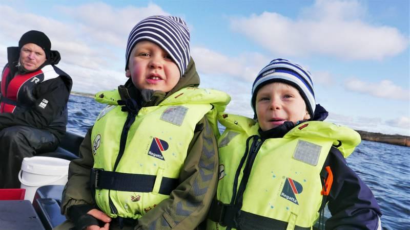 Kanskje landets yngste hummerfiskere, Wilhelm og Elliot. Bak sitter Anders og styrer båten.