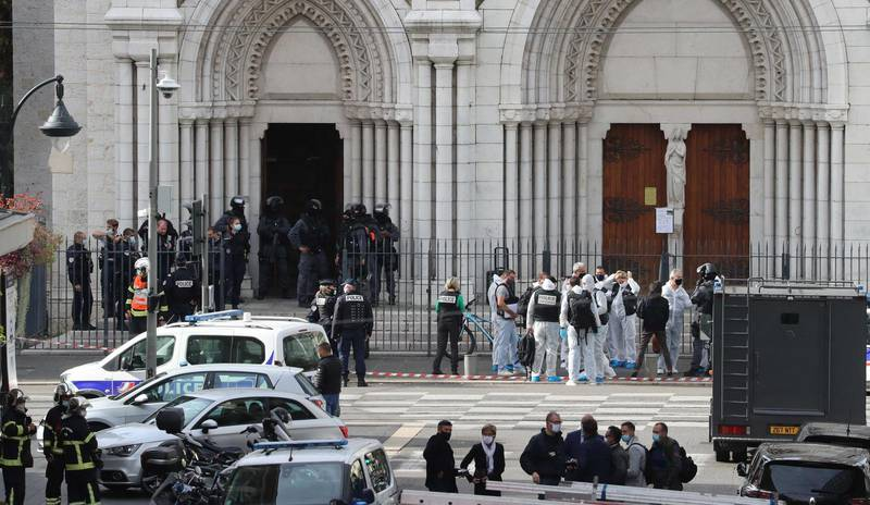 """French members of the elite tactical police unit RAID enter to search the Basilica of Notre-Dame de Nice as forensics officers wait after a knife attack in Nice on October 29, 2020. - France's national anti-terror prosecutors said Thursday they have opened a murder inquiry after a man killed three people at a basilica in central Nice and wounded several others. The city's mayor, Christian Estrosi, told journalists at the scene that the assailant, detained shortly afterwards by police, """"kept repeating 'Allahu Akbar' (God is Greater) even while under medication."""" He added that President Emmanuel Macron would be arriving shortly in Nice. (Photo by Valery HACHE / AFP)"""