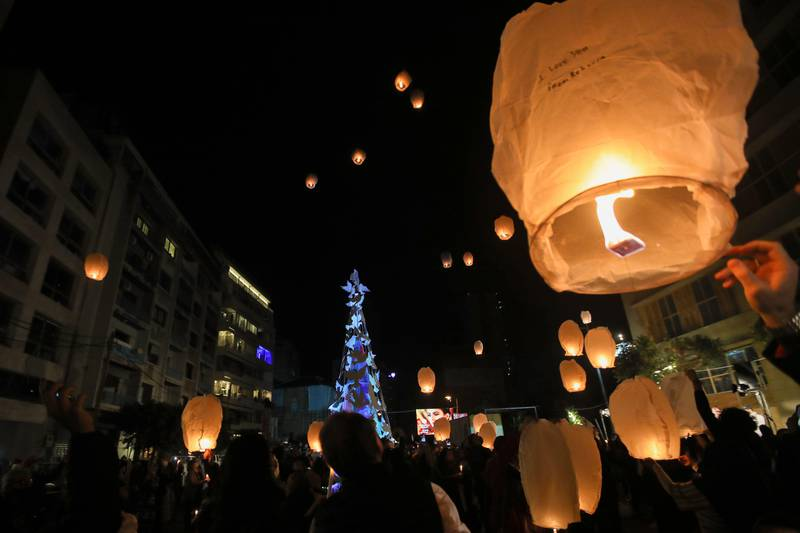 Lebanese launch lanterns in Beirut's Gemmayzeh neighbourhood on December 20, 2020, during the lighting of a Christmas tree in memory of the victims of the devastating port blast in that took place in the capital's port in August. (Photo by ANWAR AMRO / AFP)