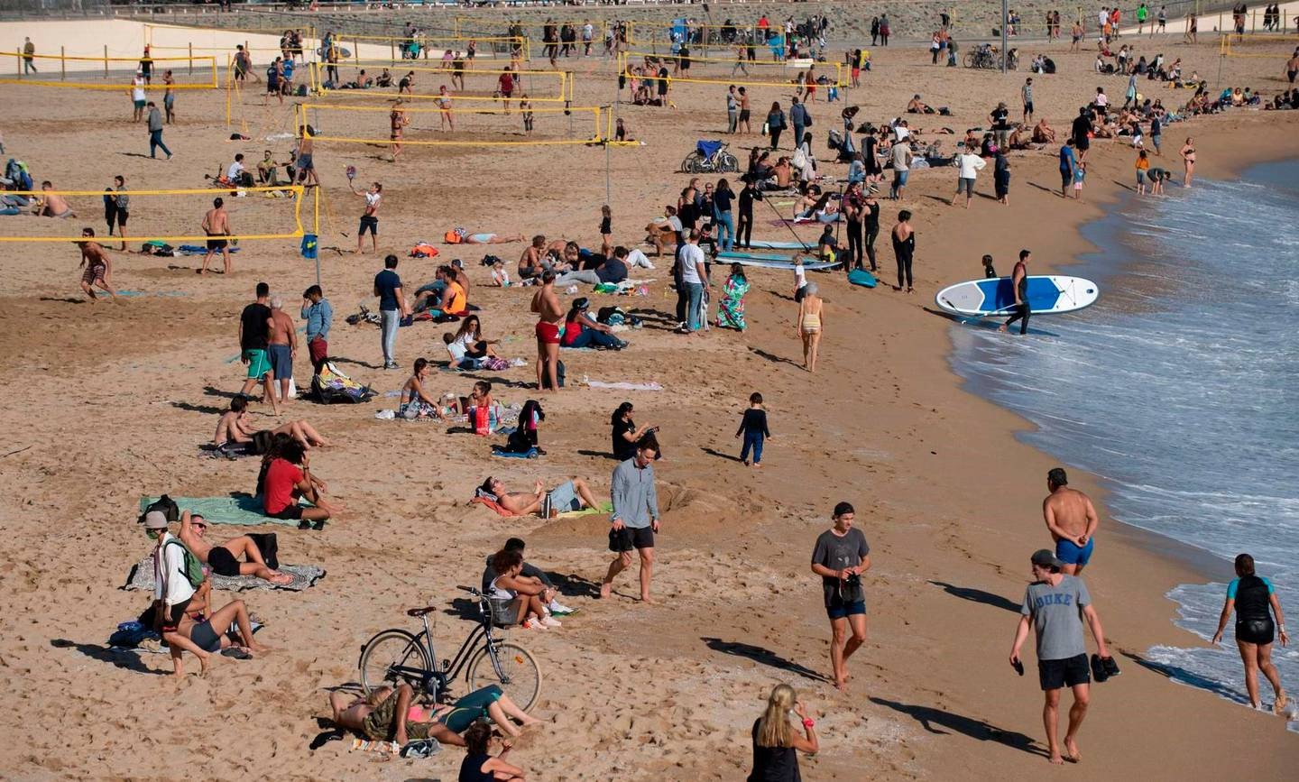 People sunbathe at the Bogatell beach in Barcelona, one of the several sands of the city that have been closed to leisure bathing amid the coronavirus panemic, in Barcelona on November 8, 2020. (Photo by Josep LAGO / AFP)