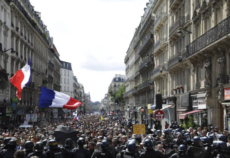 Demonstranter vifter med franske flagg under en ny protest i Paris mot myndighetenes planlagte påbud om såkalt koronapass. Foto: Adrienne Surprenant / AP / NTB