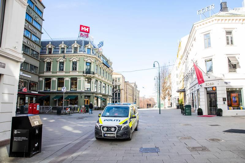Oslo 20200313.  En politibil kjører over et nesten folketomt Egertorget på Karl Johans gate i Oslo fredag, dagen etter Oslo kommune og regjeringen kom med strenge tiltak for å begrense koronasmitten. Foto: Håkon Mosvold Larsen / NTB scanpix