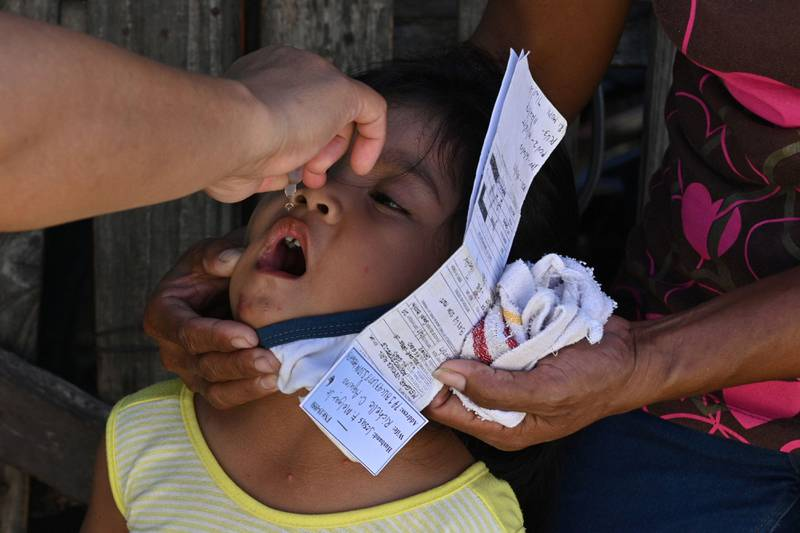 This photo taken on September 21, 2020 shows a municipal health worker (L) applying drops of a polio vaccine to child at a relocation site for informal settlers in San Jose Del Monte in Bulacan province, north of Manila. - Online misinformation is leaching out from cheap mobile phones and free Facebook plans used by millions of poor in the Philippines, convincing many to reject vaccinations for polio and other deadly diseases. (Photo by Ted ALJIBE / AFP) / TO GO WITH Health-virus-misinformation-internet-vaccine-Philippines,FOCUS by Jake Soriano