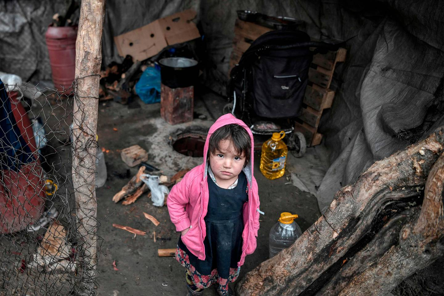 A child looks on from its family shelter at the overcrowded Moria migrant camp on the island of Lesbos, on March 5, 2020. - Greece's defence ministry on March 5 announced a week-long shipping ban around Aegean islands facing a migration surge from Turkey, excepting only EU and NATO patrol vessels and registered commercial ships. Greece is attempting to hold back a migration surge by land and sea from neighbouring Turkey that began last week after Ankara said it would no longer stop asylum seekers from entering Europe. (Photo by LOUISA GOULIAMAKI / AFP)