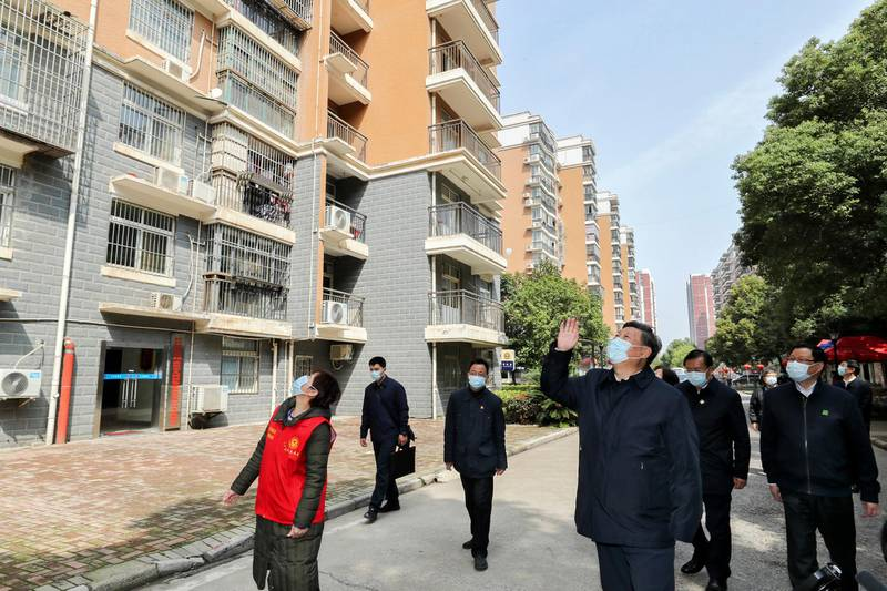 In this Tuesday, March 10, 2020, photo released by Xinhua News Agency, Chinese President Xi Jinping waves to residents who are quarantined at home as he pays a visit to a community in Wuhan in central China's Hubei province. The province at the center of China's virus outbreak is allowing factories and some other businesses to reopen in a new sign Beijing believes the disease that devastated its economy is being brought under control. (Ju Peng/Xinhua via AP)