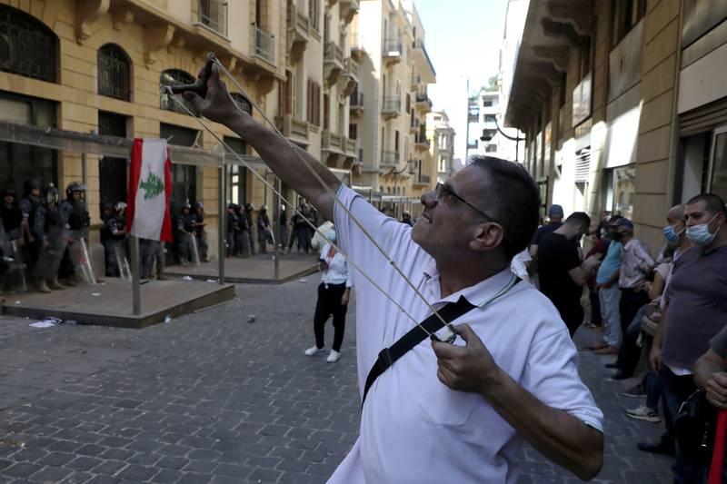 En mann skyter stein mot en bank i Beirut med sprettert. En folkemengde samlet seg onsdag utenfor banken for å kreve å få ut penger som er blitt blokkert på kontoene som følge av landets dype økonomiske krise. Lørdag kom meldingen om at strømforsyningen i landet kan bli borte i mange dager. Foto: Bilal Hussein / AP / NTB