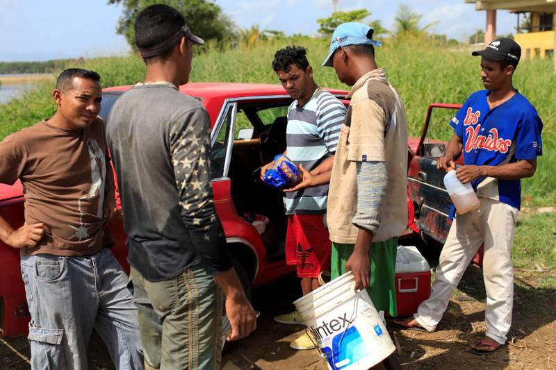 Hyperinflasjon: Mennene bytter en pakke pasta mot fisk i Rio Chico, Venezuela. FOTO: MARCO BELLO/NTB SCANPIX
