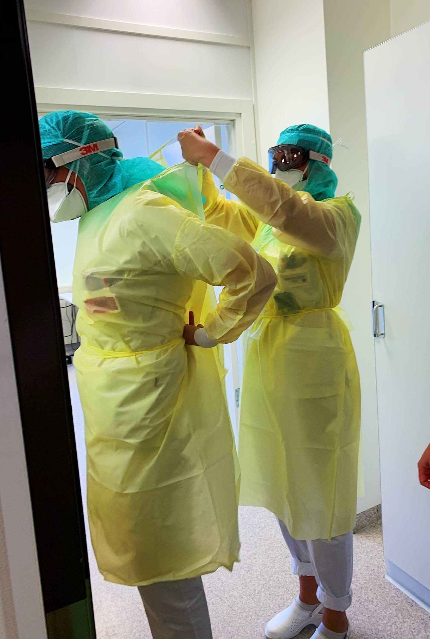 Sykepleiere ved akuttmottaket på Drammen sykehus forbereder seg på å gå inn til pasient som har testet positivt på korona.