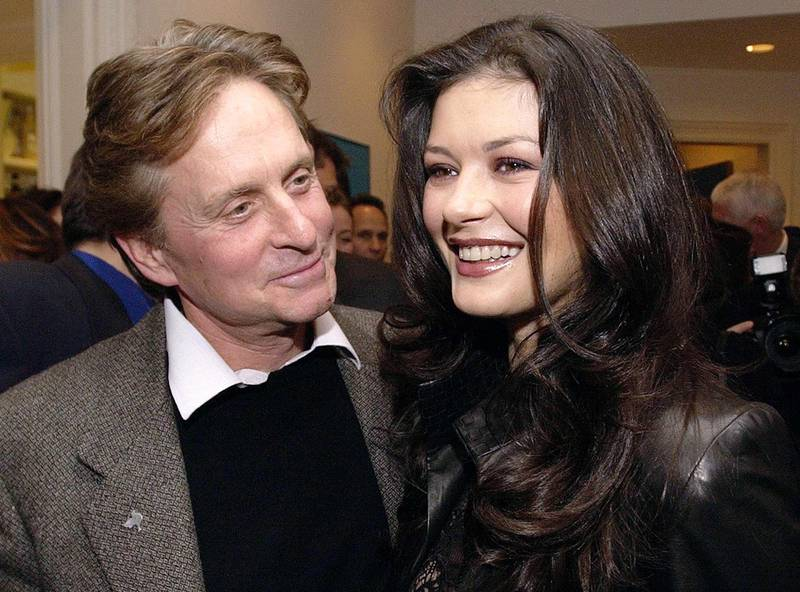 Actors Michael Douglas, left, and wife Catherine Zeta-Jones smile at a private party in honor of former South African President Nelson Mandela in Toronto Saturday, Nov. 17, 2001. Mandela and his wife, Graca Machel, were in Toronto for a brief weekend visit to receive honorary doctorates of laws from Ryerson for their work with children. (AP Photo/CP, Aaron Harris)
