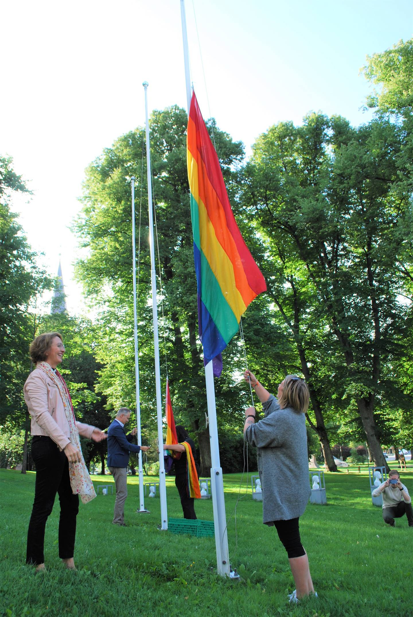 Domprost i Fredrikstad, Kari Mangrud Alvsvåg og styremedlem Hege Hansen i Fredrikstad Pride heiser regnbueflagget utenfor Fredrikstad rådhus. I bakgrunnen ordfører Jon-Ivar Nygård.