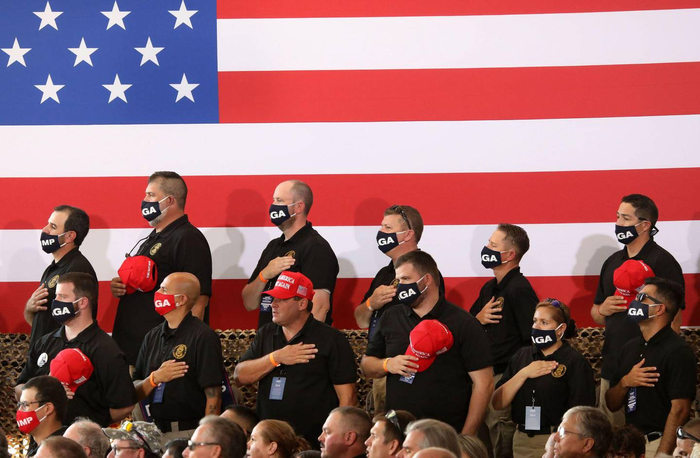 YUMA, AZ - AUGUST 18: Supporters of U.S. President Donald Trump stand for the national anthem before a campaign rally at The Defense Contractor Complex on August 18, 2020 in Yuma, Arizona. Trump excoriated presumptive Democratic nominee former Vice President Joe Biden as being soft on illegal immigration as Democrats hold their convention this week remotely from Milwaukee. Hundreds waited in line in 104-degree heat to see the president, many without masks or maintaining distance from others, according to published reports. The crowd size inside the hangar was limited in a nod to the ongoing pandemic that has hit Yuma County particularly hard.   Sandy Huffaker/Getty Images/AFP == FOR NEWSPAPERS, INTERNET, TELCOS & TELEVISION USE ONLY ==