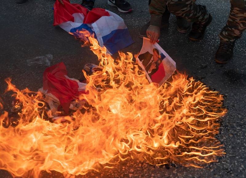 Palestinian protesters burn representa French flags and pictures of French President Emmanuel Macron during a protest against the publishing of caricatures of the Prophet Muhammad they deem blasphemous, in the West Bank city of Ramallah, Tuesday, Oct. 27, 2020.