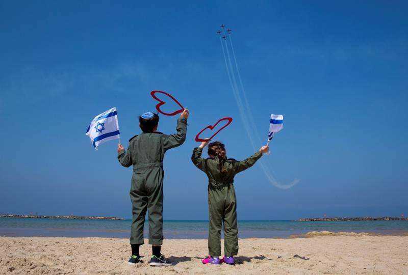 Israelske barn i pilotuniformer og med israelske flagg jubler til de israelske luftvåpenet trener for dagens store festoppvisning i Tel Aviv.