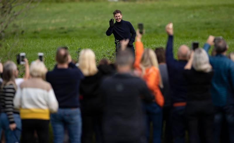 Hellesylt 20200906.  Skuespiller Tom Cruise hilser og tar farvel med bygdefolket etter at han hadde gjennomført sine halsbrekkende stunt i luften over Hellesylt ved Helsetkopen i anledning av opptakene av den neste «Mission: Impossible»-filmen. Etter flere dagers venting gjennomførte actionhelten fire hopp med motorsykkel ut fra den enorme rampen på fjelltoppen Helsetkopen ved Hellesylt i Stranda Kommune. Syklene landet i ura, mens Cruise svevet ned den bratte fjellsiden i fallskjerm. Foto: Geir Olsen / NTB scanpix