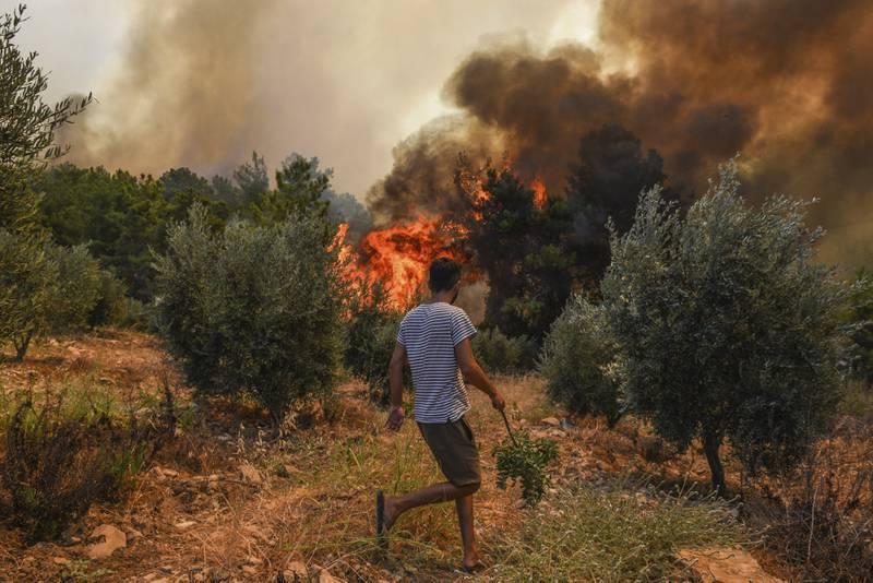En skogbrann herjer i landsbyen Kacarlar ved Manavgat i Antalya lørdag. Foto: AP / NTB