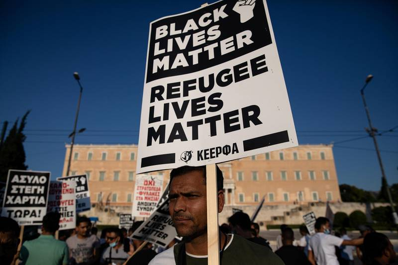 """A migrant holds a placard reading """"Black Lives Matter, Refugee Lives Matter"""" during a demonstration outside the Greek parliament against a government decision that refugees staying in apartments funded by a European Union and UNHCR programme should leave their accommodation, in Athens, Greece, June 26, 2020. REUTERS/Alkis Konstantinidis"""