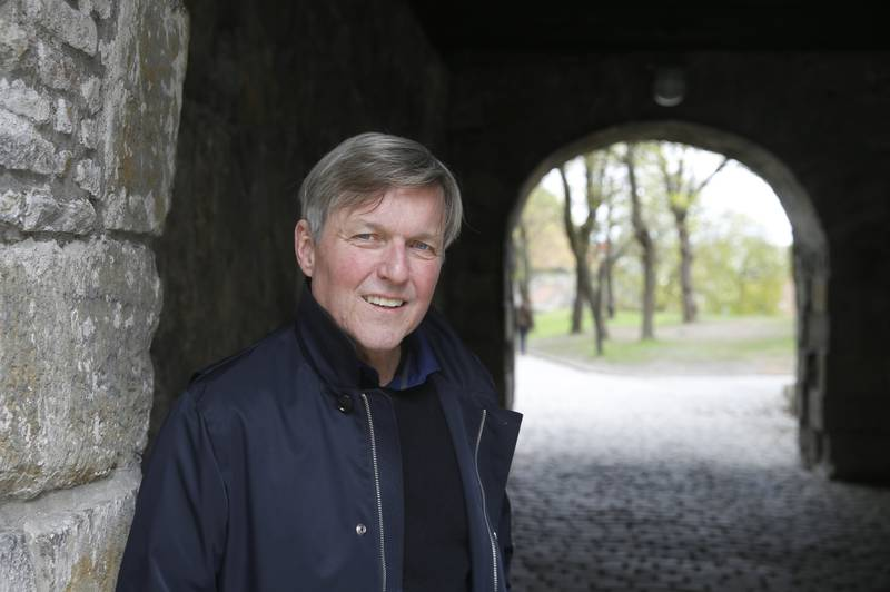 Jan Ove Ekeberg i mørk jakke står i en vollportmur i Gamlebyen Fredrikstad