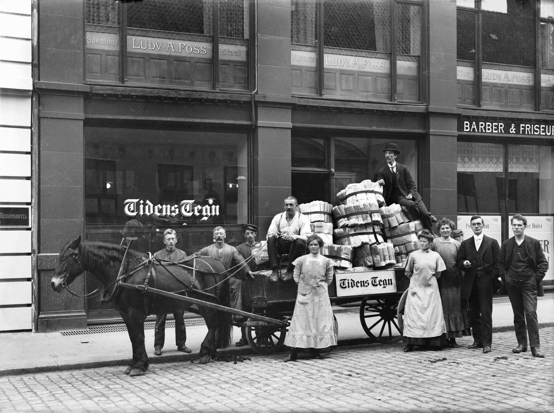 Beskjørtete og buksekledte avisansatte fotografert utafor arbeidsplassen Tidens Tegn i Rådhusgata 20 cirka 1915.