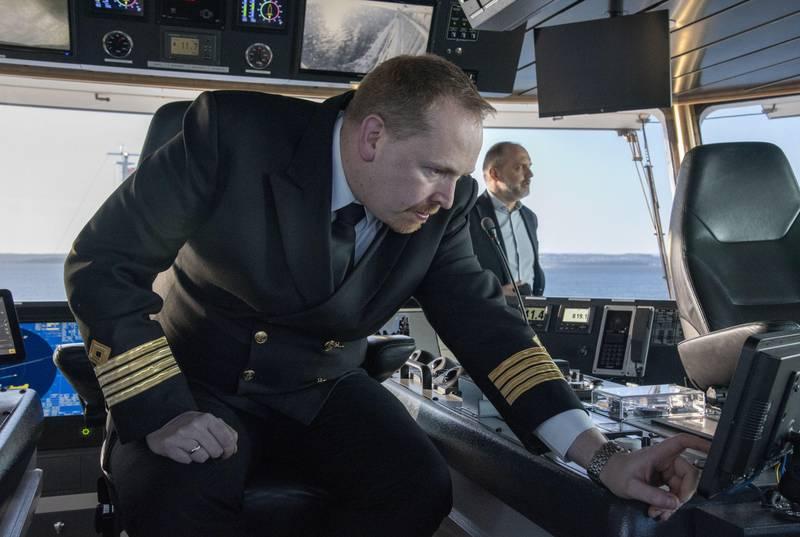 Kaptein Christian Larsen sjekker autonomifunksjonen på Bastøferja. Skipet kan nå seile over Oslofjorden uten at han eller andre fra mannskapet bør ta i roret. I bakgrunnen ser vi adm. direktør Øyvind Lund i Bastø Fosen.