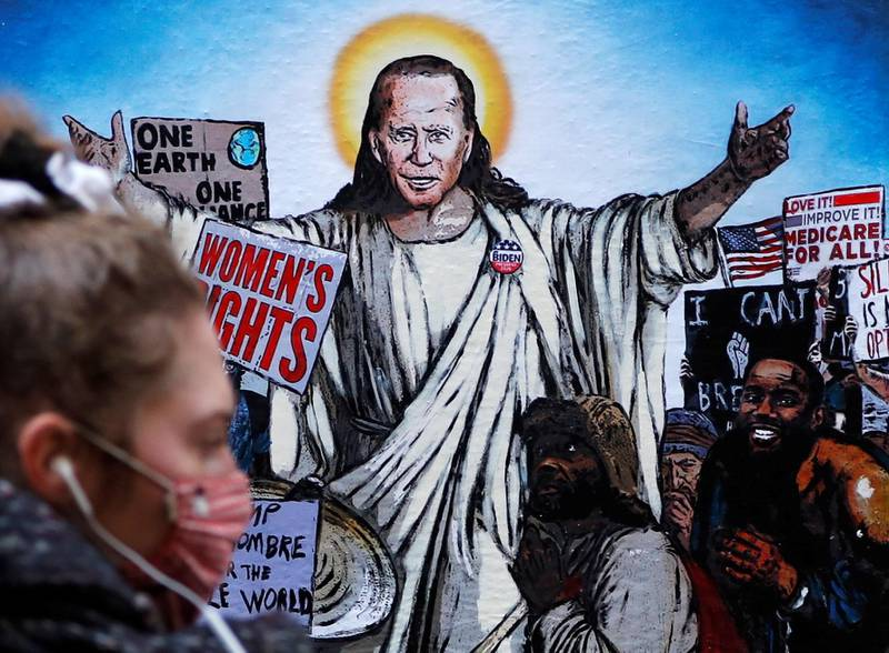 A woman walks past a mural depicting U.S. President Joe Biden as Jesus addressing crowds of people titled 'The Saviour', created by artist Harry Greb in Rome, Italy, January 21, 2021. REUTERS/Yara Nardi     TPX IMAGES OF THE DAY