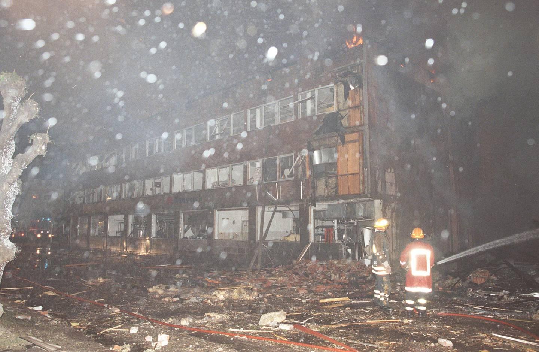 Drammen. Bandidos hovedkvarter rammet av bombeeksplosjon. En forbipasserende kvinne ble drept. - Brannmenn  spyler vann mot restene av det fullstendig ødelagte hovedkvarteret til Bandidos,  mens brannen er i ferd med å komme under kontroll i lokalene til  Drammens Is, som  er  mc-klubbens nærmeste nabo.