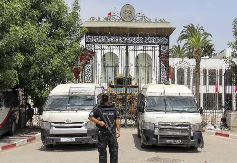 Politibiler og væpnet personell foran den stengte inngangen til Tunisias nasjonalforsamling etter at president Kais Saied søndag avsatte landets statsminister.