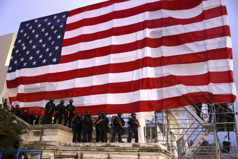 WASHINGTON, DC - JANUARY 06: Police officers in riot gear stand under a large American flag as protesters gather at the U.S. Capitol Building on January 06, 2021 in Washington, DC. Pro-Trump protesters entered the U.S. Capitol building after mass demonstrations in the nation's capital during a joint session Congress to ratify President-elect Joe Biden's 306-232 Electoral College win over President Donald Trump.   Tasos Katopodis/Getty Images/AFP == FOR NEWSPAPERS, INTERNET, TELCOS & TELEVISION USE ONLY ==